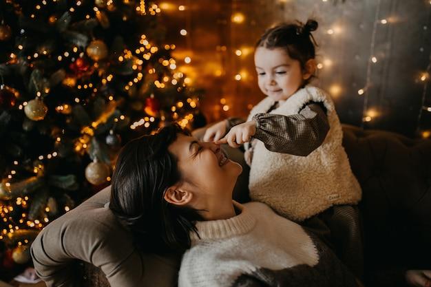 Moeder en dochter spelen op kerstavond thuis, zittend op een bank