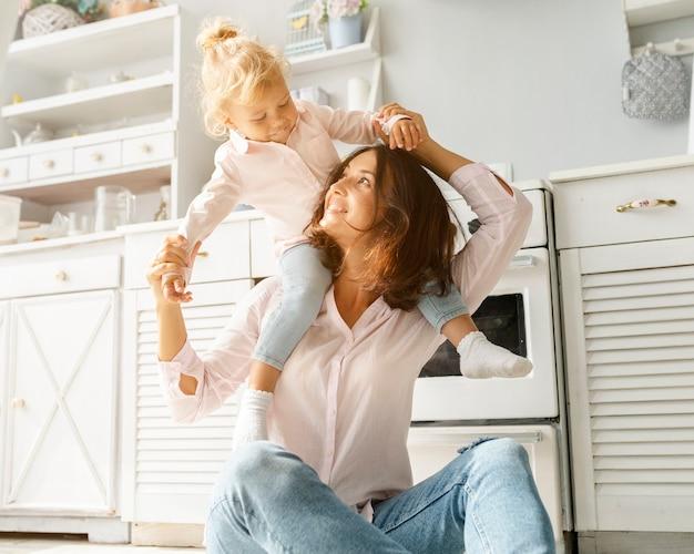 Moeder en dochter spelen op keukenvloer