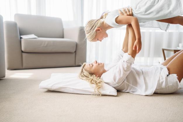 Moeder en dochter spelen samen thuis op de vloer. oudergevoel, saamhorigheid, gelukkig gezin