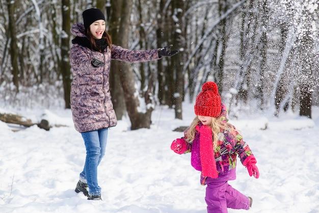 Moeder en dochter spelen sneeuwballen in winter forest