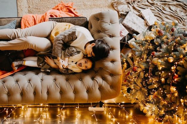 Moeder en dochter spelen thuis, liggend op een bank, naast een kerstboom