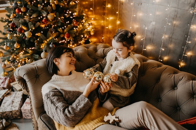 Moeder en dochter spelen thuis naast een kerstboom, zittend op een bank