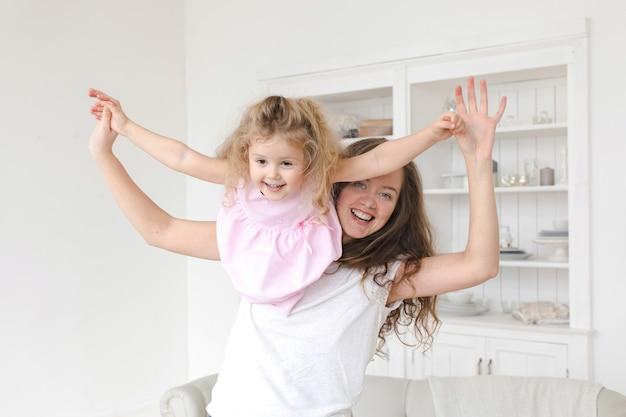 Moeder en dochter spelen vliegen dromen in het daginterieur