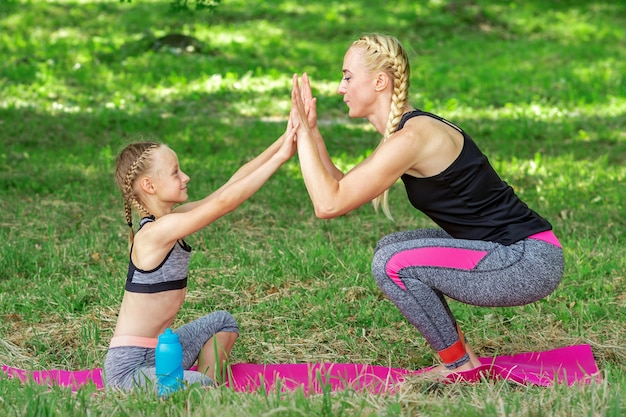 Moeder en dochter sporten oefeningen op de mat in het park buiten