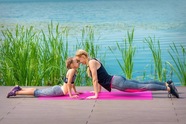 Moeder en dochter sporten oefeningen op de pier in de buurt van het water buiten
