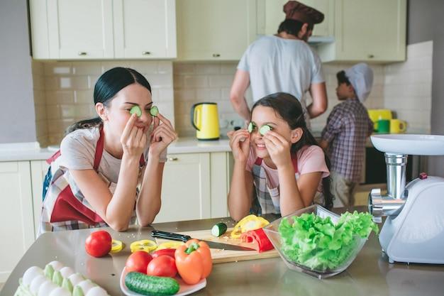 Moeder en dochter staan bij elkaar en leunen aan tafel. ze spelen met ronde stukjes komkommer.
