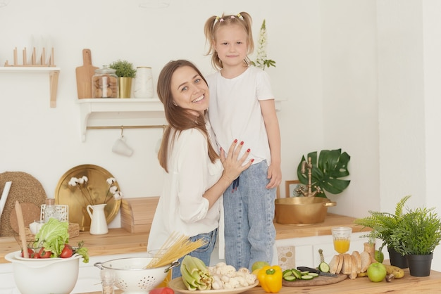 Moeder en dochter staan in de keuken van het huis, kijken naar de camera en lachen. de juiste voeding in huis. samen tijd doorbrengen.