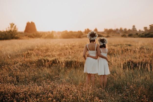 Moeder en dochter staan in de zomer terug bij zonsondergang in het veld in witte jurken en bloemenkransen