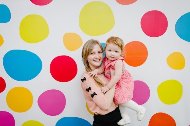 Moeder en dochter staan lachend en gelukkig op een gekleurde achtergrond. concept van vreugde. gelukkige familie, meisjes in de buurt van een kleurrijke achtergrond.