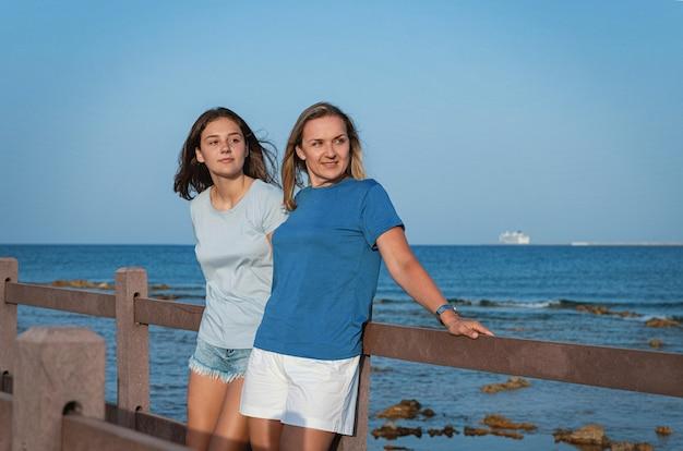 Moeder en dochter staan op houten stoep aan zee bij zonsondergang. een vrouw van middelbare leeftijd en een tienermeisje staan naast elkaar en dragen blauwe t-shirts en spijkerbroeken. moederschap concept