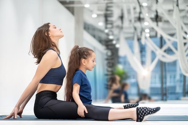 Moeder en dochter strekken zich uit voordat ze gaan sporten