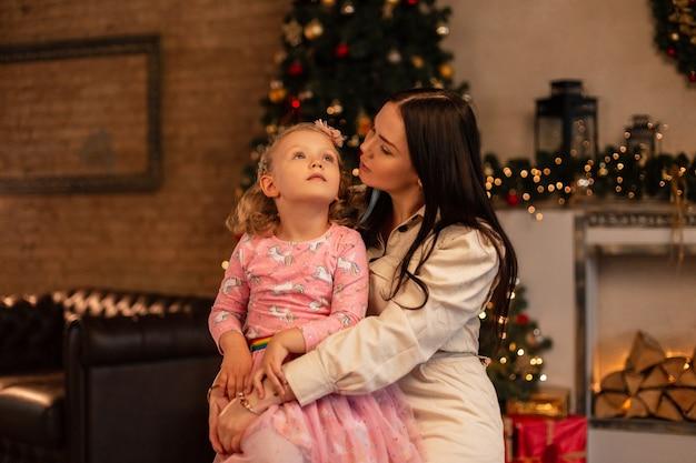 Moeder en dochter tegen de achtergrond van kerstdecor thuis