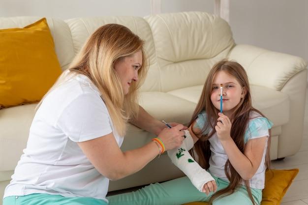 Moeder en dochter tekenen foto op verband met behulp van verven speltherapie concept