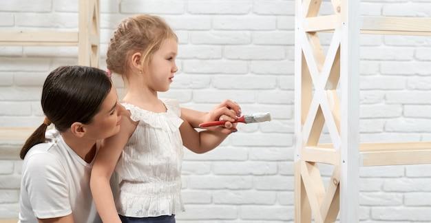 Moeder en dochter tijdens het schilderen van rek thuis