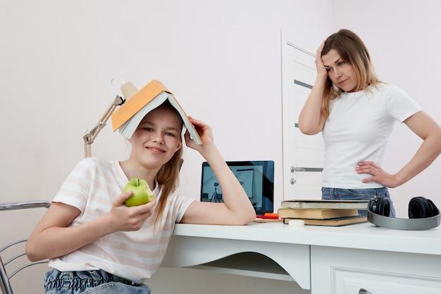 Moeder en dochter vechten om huiswerk, boos moeder is boos op kleine verveelde dochter, thuisonderwijs, misverstand