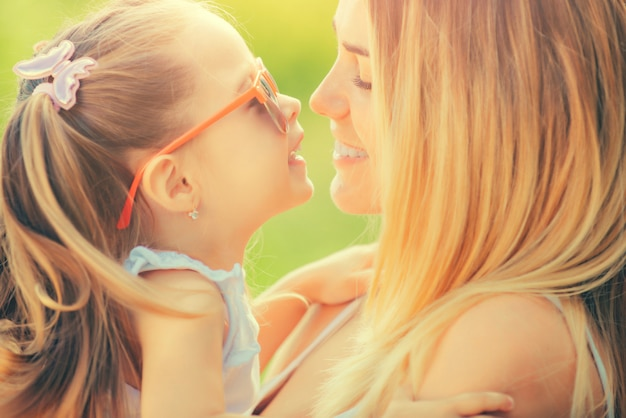 Moeder en dochter verliefd. gelukkige familie meisjes knuffelen en kussen.
