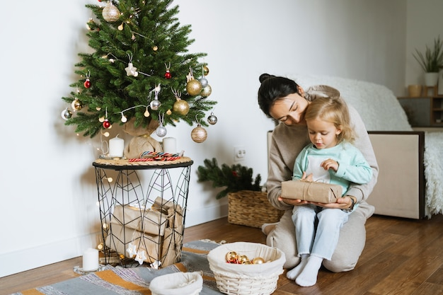 Moeder en dochter versieren de kerstboom in de kamer. vrolijk kerstfeest en een gelukkig nieuwjaarsconcept. ruimte voor tekst. gezellige momenten voor het hele gezin.