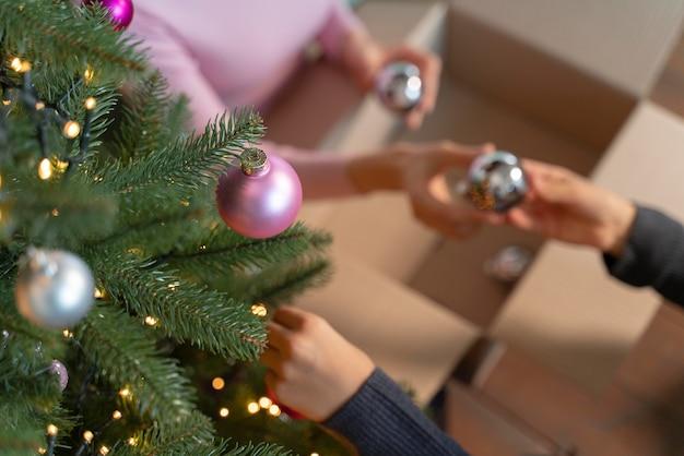 Moeder en dochter versieren de kerstboom