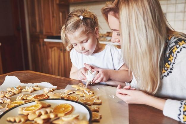 Moeder en dochter versieren het kerstkoekje met witte suiker