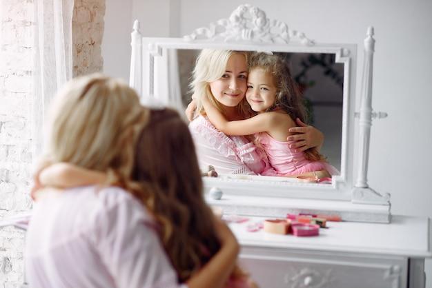 Moeder en dochter verzamelen zich in de ochtend voor een spiegel