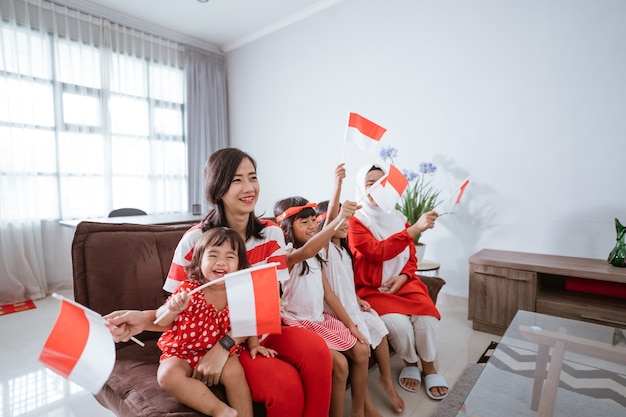 Moeder en dochter vieren de indonesische onafhankelijkheidsdag thuis in rood en wit met indones...