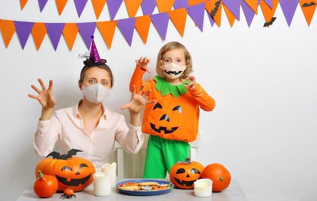 Moeder en dochter vieren halloween. familie die gezichtsmaskers draagt die beschermen tegen covid-19.