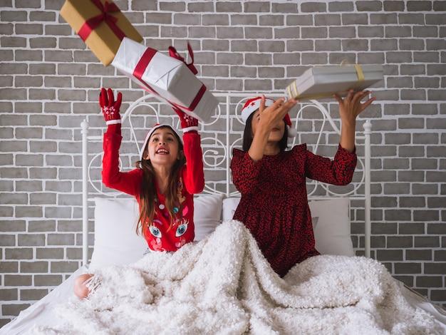 Moeder en dochter vieren kerstmis door een geschenkdoos in de lucht te gooien