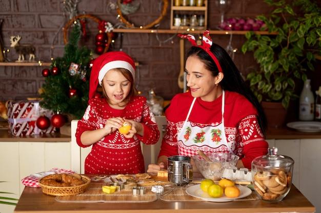 Moeder en dochter voeden elkaar mandarijnen in een donkere keuken met een kerstboom en koken gemberkoekjes voor nieuwjaar of kerstmis, glimlachen en hebben samen plezier in afwachting van de vakantie