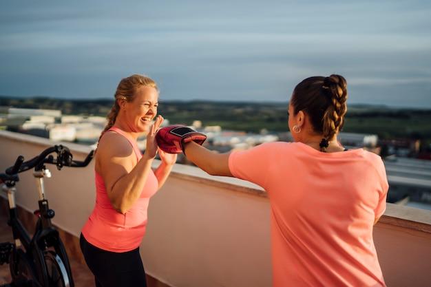 Moeder en dochter voeren boksoefeningen uit op huisterras