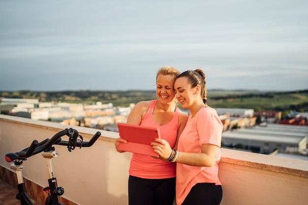 Moeder en dochter voeren gymnastiekoefeningen op huisterras uit gebruikend tablet