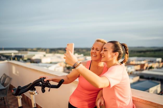 Moeder en dochter voeren gymnastiekoefeningen uit op huisterras met behulp van mobiele telefoon