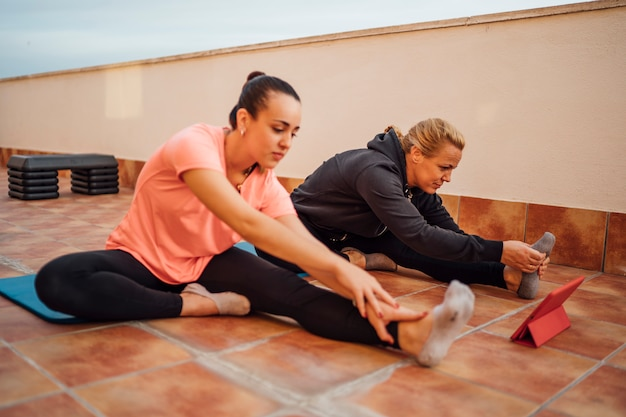 Moeder en dochter voeren gymnastiekoefeningen uit op huisterras