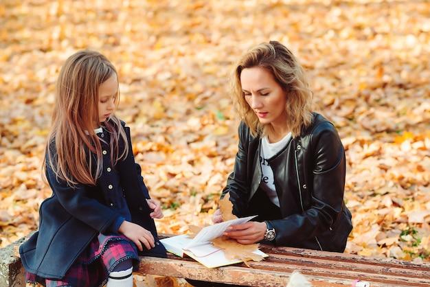 Moeder en dochter wandelen in herfst park.