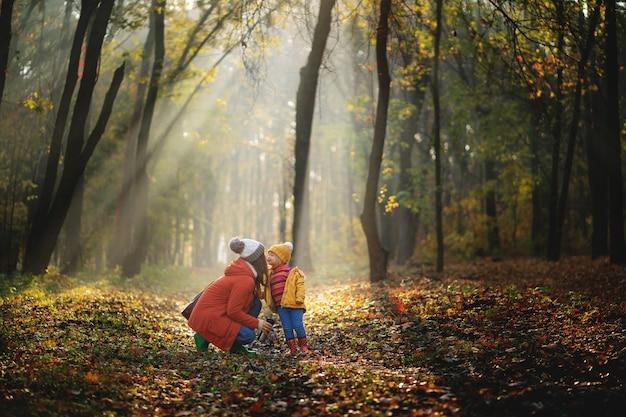 Moeder en dochter wandelen in het park en genieten van de prachtige herfst natuur.