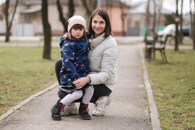 Moeder en dochter wandelen in het park tijdens qurantijnse gelukkige familie adem frisse lucht in