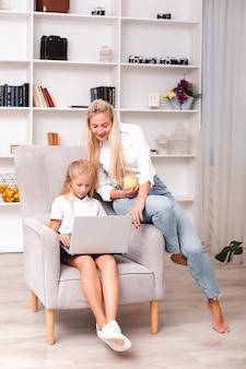 Moeder en dochter werken thuis op de computer