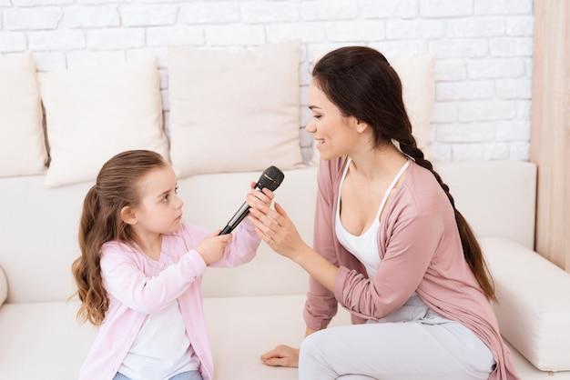 Moeder en dochter zingen thuis liedjes.