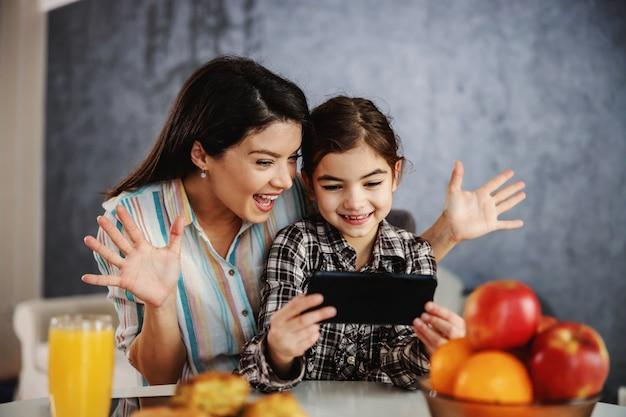 Moeder en dochter zitten aan de eettafel in de ochtend en nemen selfie.