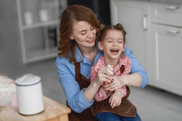 Moeder en dochter zitten aan de keukentafel en lachen