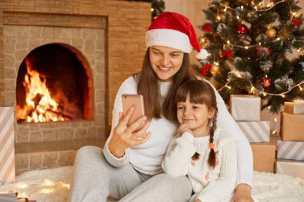 Moeder en dochter zitten in de buurt van de kerstboom, knuffelen, communiceren via videogesprek, plezier maken.