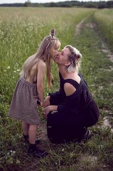 Moeder en dochter zitten in de zomer in het veld en kussen elkaar