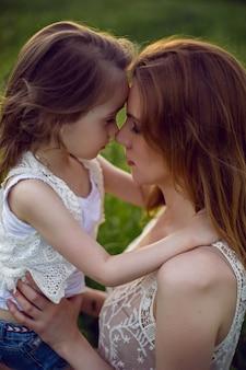 Moeder en dochter zitten in een groen veld in een wit t-shirt