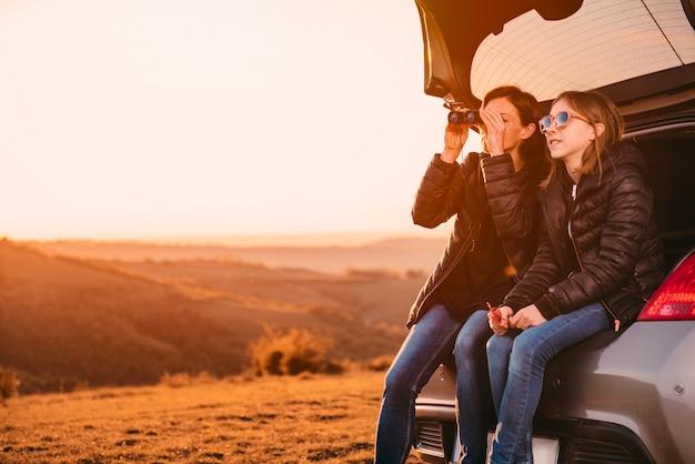 Moeder en dochter zitten in een kofferbak en het gebruik van een verrekijker
