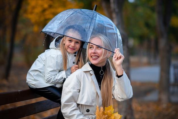 Moeder en dochter zitten in het park op een bankje onder een doorzichtige paraplu. herfstpark, familiedag