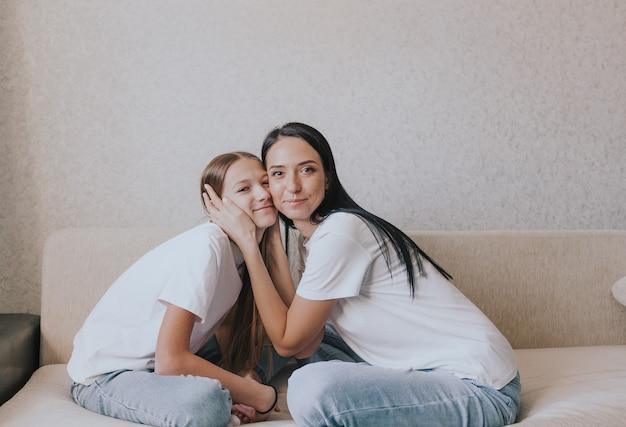 Moeder en dochter zitten knuffelend op de bank, een groot portret.