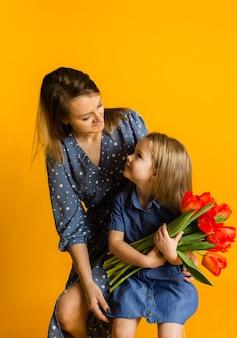 Moeder en dochter zitten met een boeket rode tulpen en kijken elkaar aan op een gele achtergrond
