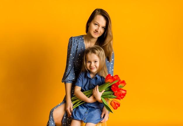Moeder en dochter zitten met een boeket rode tulpen en kijken naar de camera op een gele achtergrond