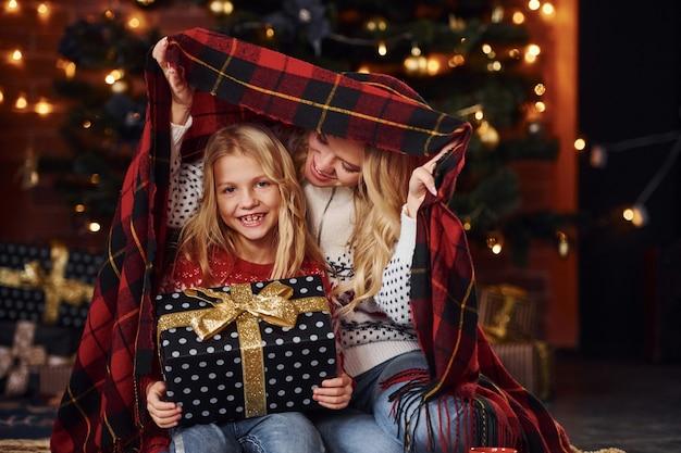 Moeder en dochter zitten onder een plaid met geschenken die samen kerstvakantie vieren.