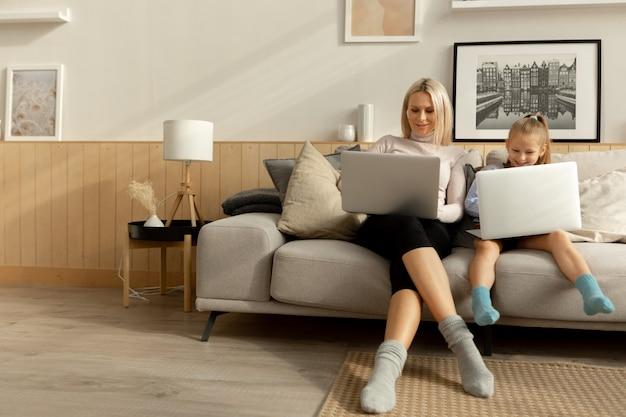 Moeder en dochter zitten op de bank in de woonkamer en kijken elk naar hun laptop