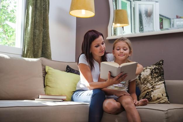 Moeder en dochter zitten op de bank lezen